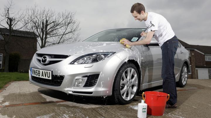 mann wäscht auto mit schwamm